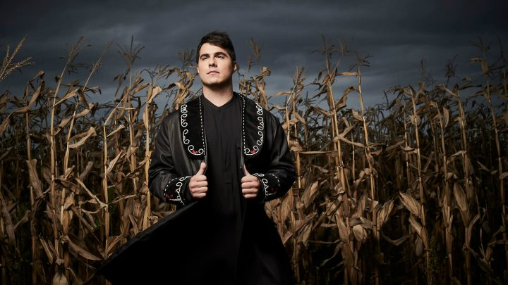 Photo of Indigenous musician Jeremy Dutcher in field at night.