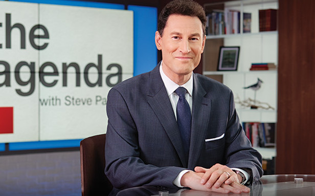 photo of steve paikin sitting on a desk in front of a screen
