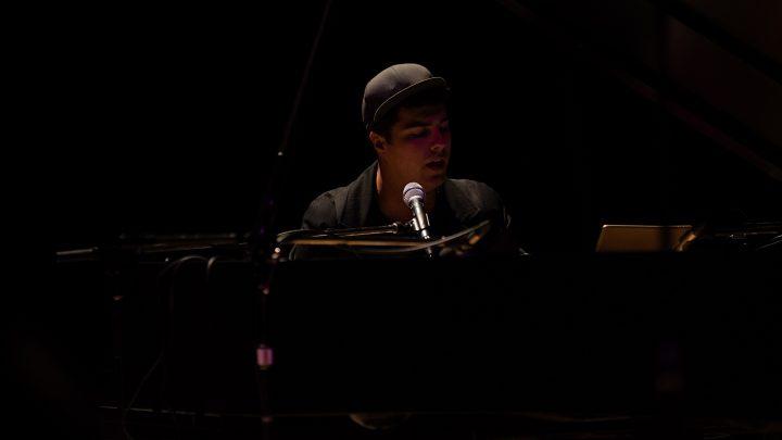 man wearing a cap playing piano