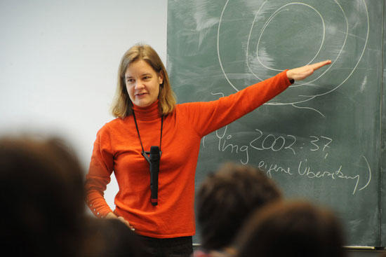 woman in a sweater pointing at a blackboard